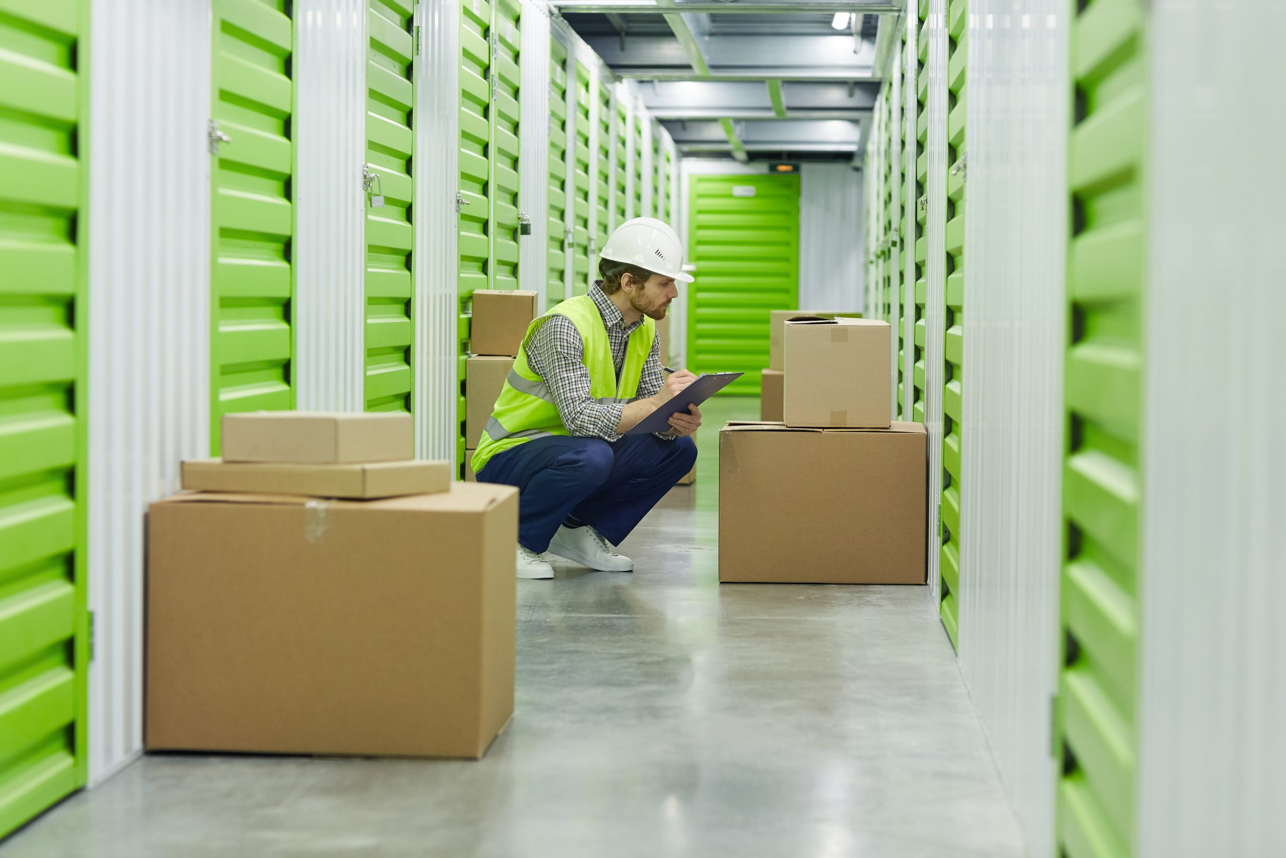 Worker in work helmet sitting and writing in document he checking boxes before delivering in warehouse